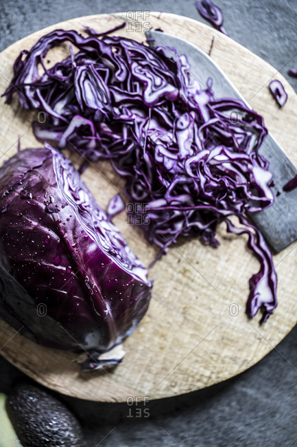 Head of purple cabbage being chopped on a wooden cutting board