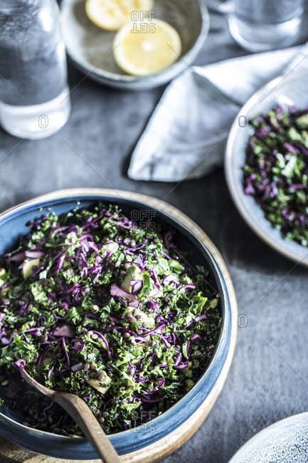 Chopped salad with cabbage, kale, avocado and lentils in a blue serving dish
