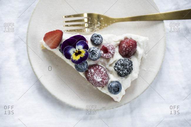 Slice of cake with berries and a pansy flower on a plate