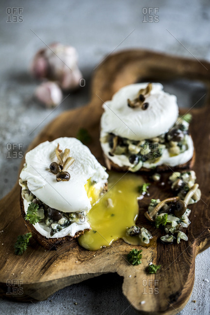Toast topped with mushrooms and poached eggs on a wooden board