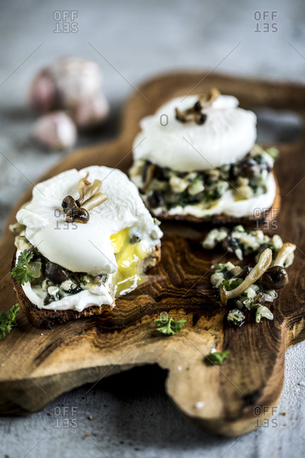 Toast on a wooden board topped with mushrooms and poached eggs