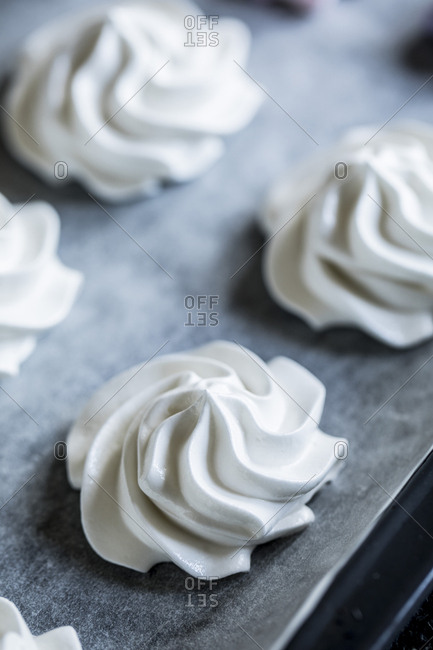 Swirled meringue in rows on a baking sheet