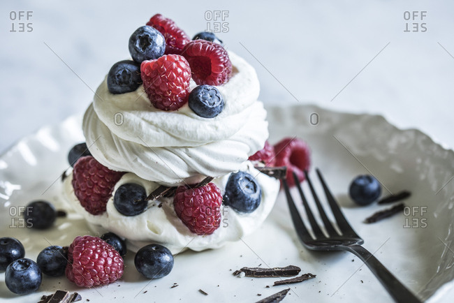 Swirls of meringue and cream on a plate with fresh berries and shaved chocolate