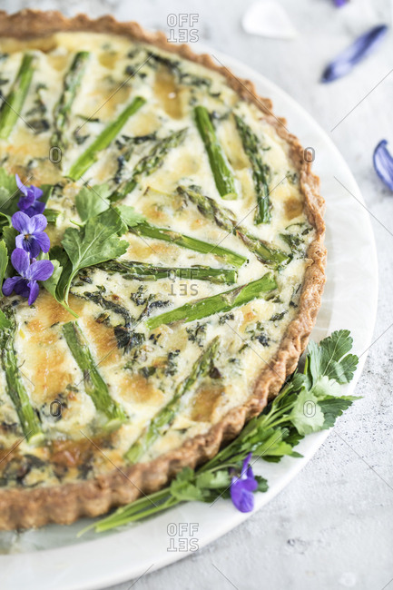 Whole baked asparagus quiche garnished with purple flowers