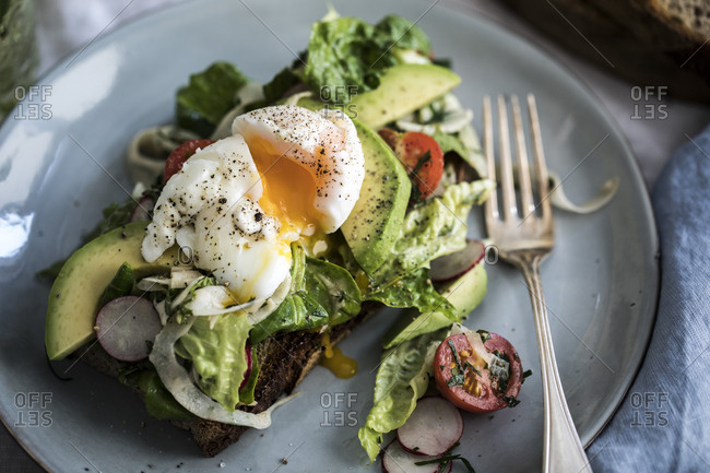 Plate with toast topped with a soft-boiled egg, avocado and salad