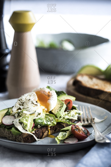 Soft-boiled egg and avocado salad on a piece of toast