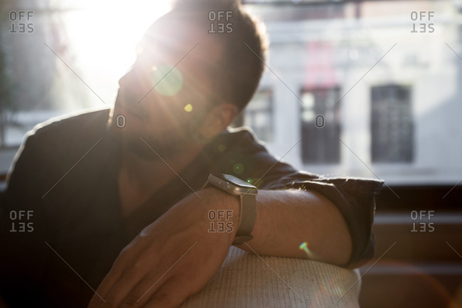 Man wearing a smart watch in a sun drenched room