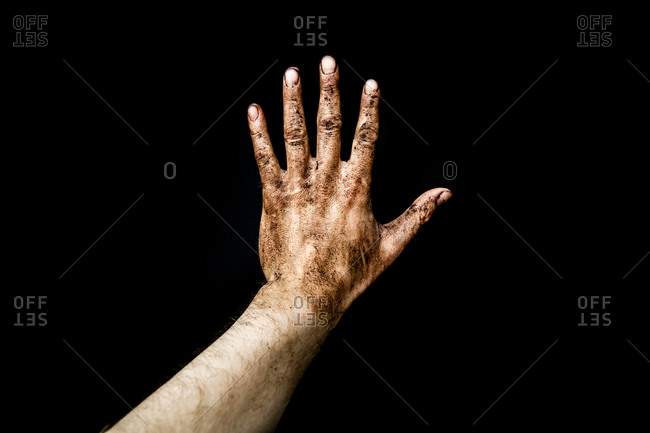 The dirt covered hand of a farmer against a black background