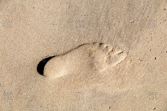 Imprint of a foot in the sand on the beach