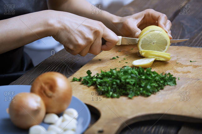 Woman cutting lemon and vegetables