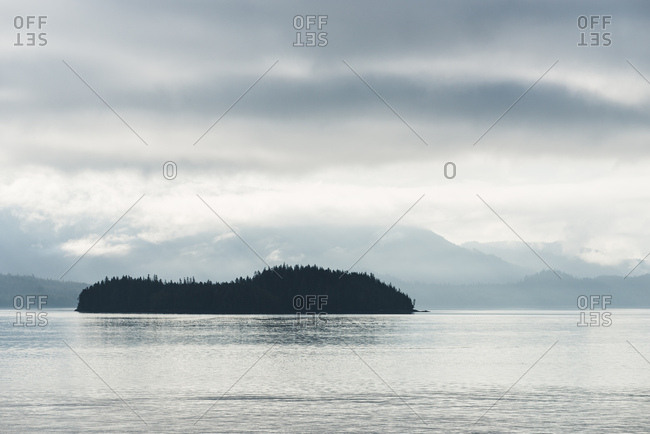 Silhouettes of trees and shrouded mountains under a ceiling of grey clouds