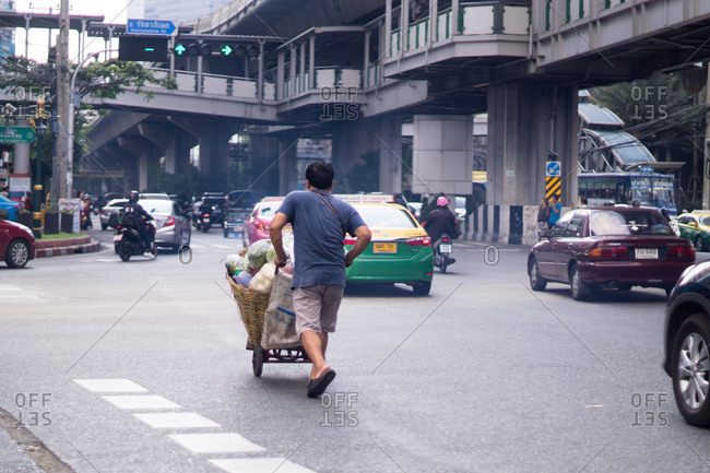 Bangkok, Thailand - February 27, 2015: Street vendor pushing a cart full of goods down a busy roadway