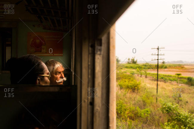Bangkok, Thailand - March 21, 2015: Two men looking out a train window