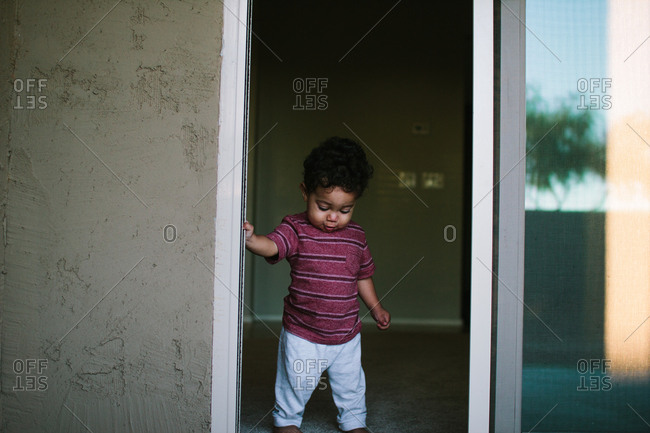 Toddler boy standing at doorway