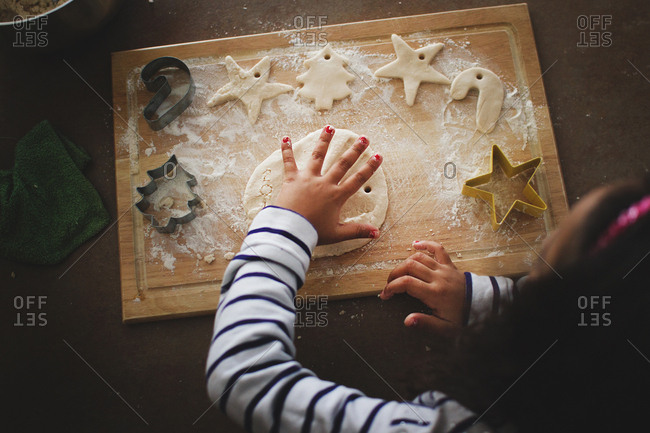 Girl cutting out holiday shaped cookies