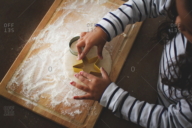 Girl cutting out star shaped cookie