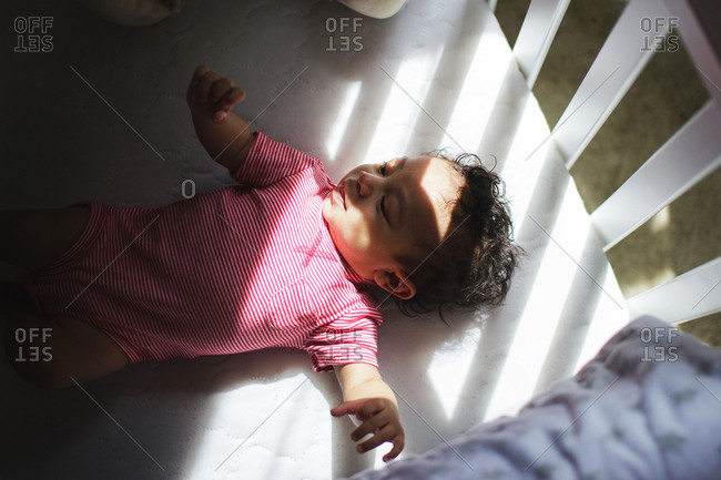 Baby lying in light in crib