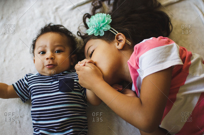 Girl kissing her baby brother