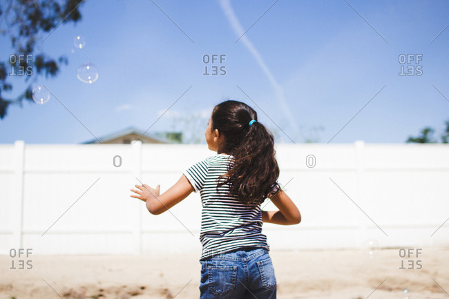 Girl watching floating bubbles