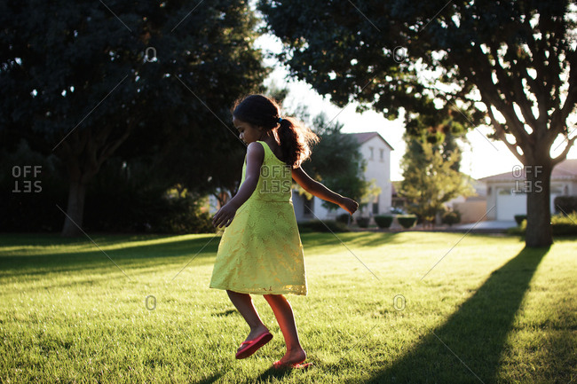 Girl dancing around in summer sunlight