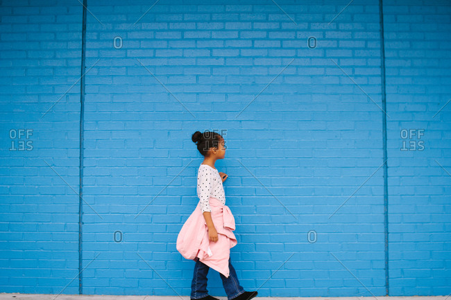 Girl walking by blue brick wall