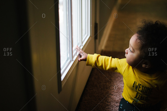 Toddler boy in sunlight from door