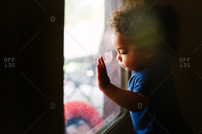 Toddler boy pressed to window