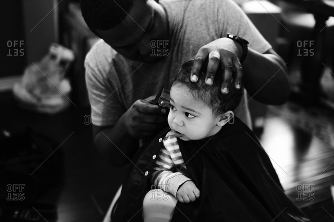 Dad trimming toddler boy's hair