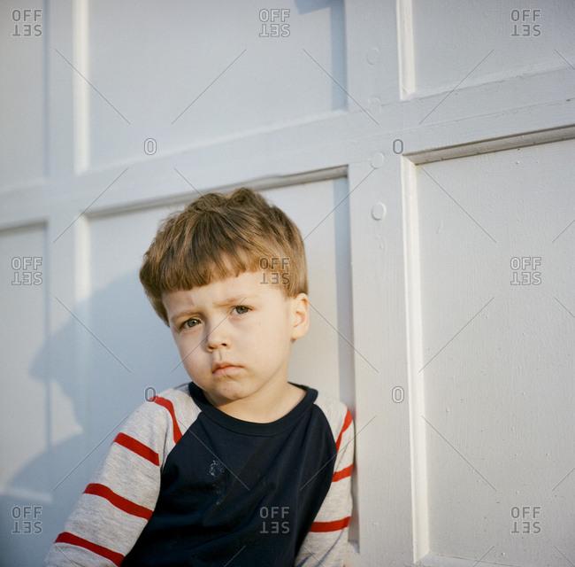 Boy in sunlight by wall in house
