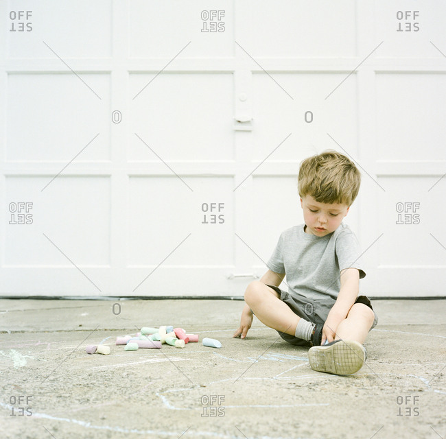 Boy drawing on driveway with chalk
