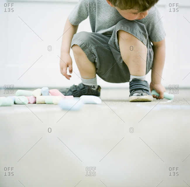 Boy drawing on cement with chalk