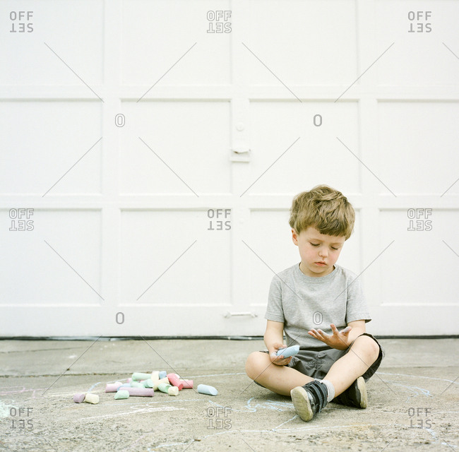 Boy playing on driveway with chalk