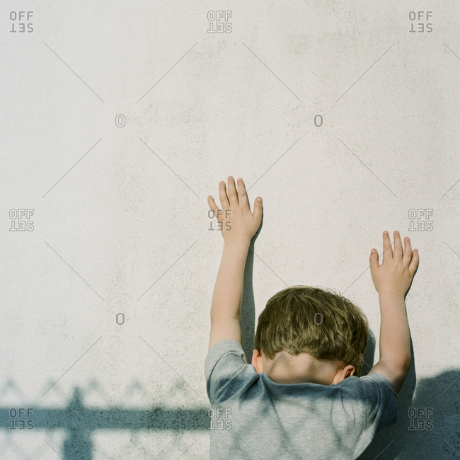 Boy at wall with fence shadow