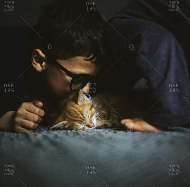 Kids kissing a sleeping cat