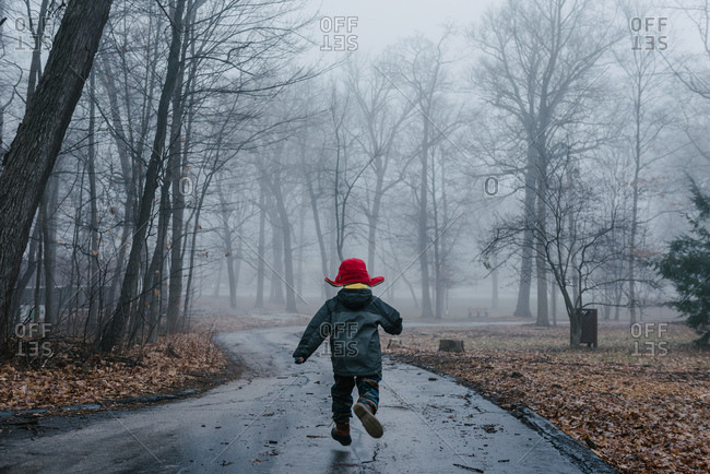 Boy running down a foggy path