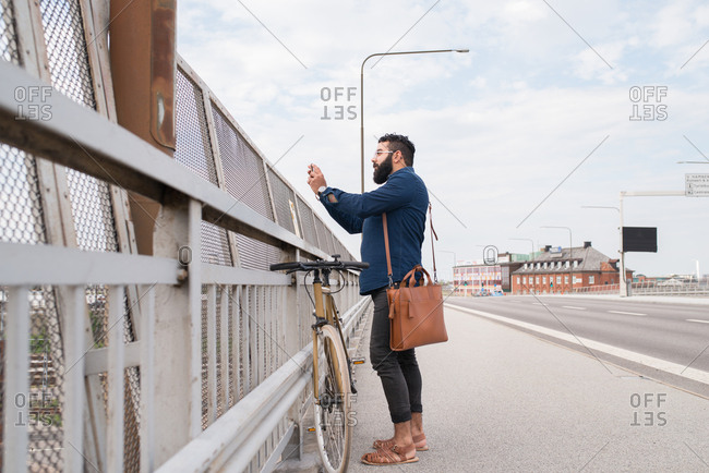 Man with bicycle standing on bridge taking a picture