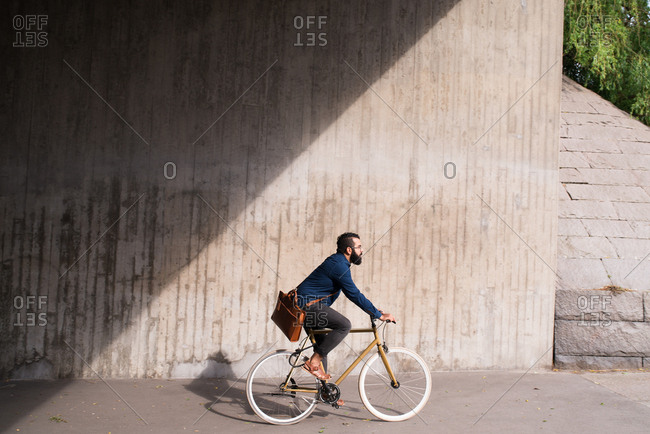 Man with messenger bag riding bicycle on sidewalk