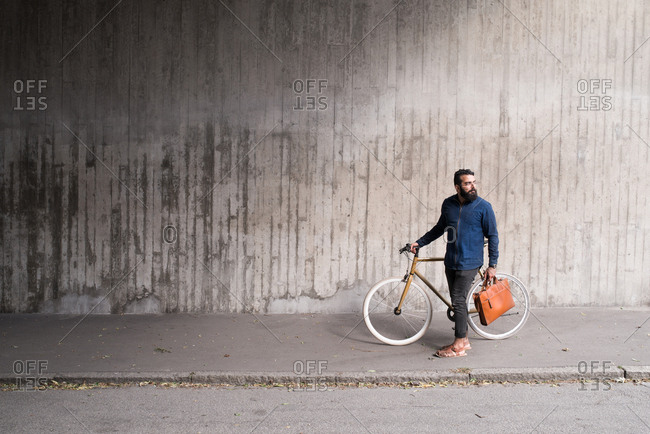 Man holding messenger bag standing with bicycle on sidewalk