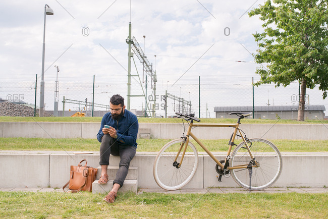 Young man using his smartphone sitting next to bicycle