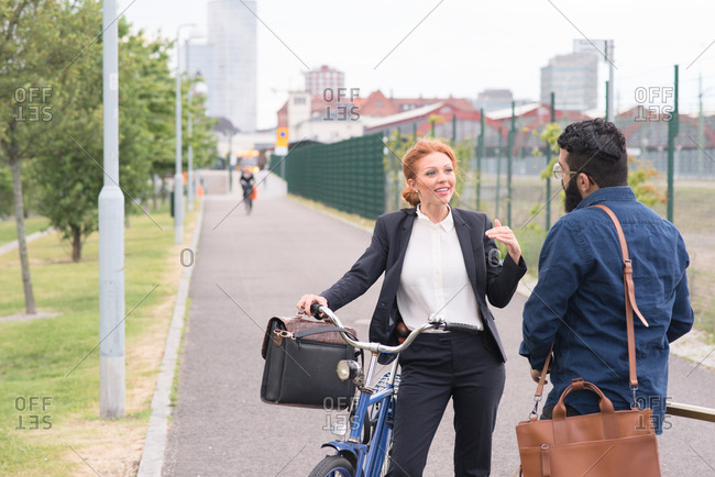 Two businesspeople standing on bike path talking with each other