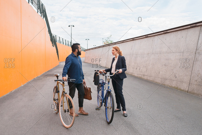 Two businesspeople talking with each other standing next to bikes on path