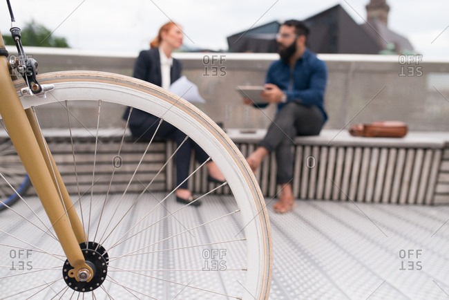 Bicycle wheel and two businesspeople sitting together