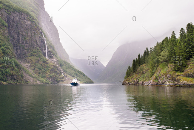 Boat on narrow waterway between forested cliffs