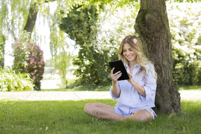 Woman sitting by tree using digital tablet