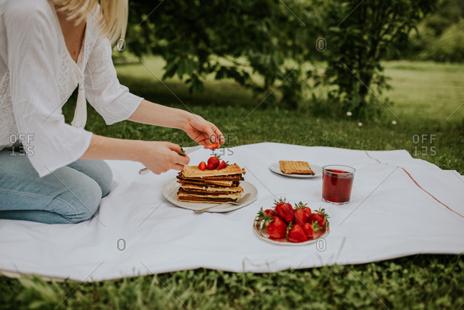 Blonde woman topping Belgium waffles with strawberries