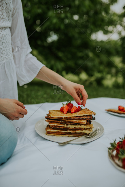 Woman topping Belgium waffles with strawberries