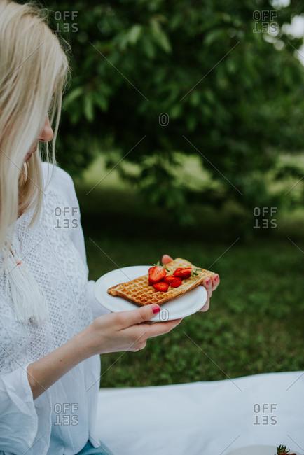 Blonde woman eating Belgium waffles with strawberries