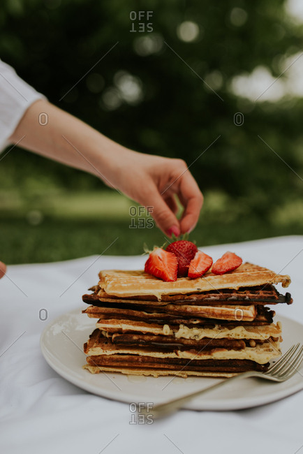 Person topping Belgium waffles with strawberries