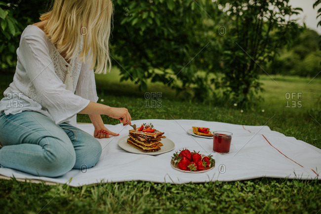 Blonde woman eating Belgium waffles with strawberries on a picnic blanket