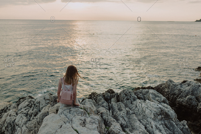 Young woman overlooking sea from rocky coast of Rovinj, Croatia